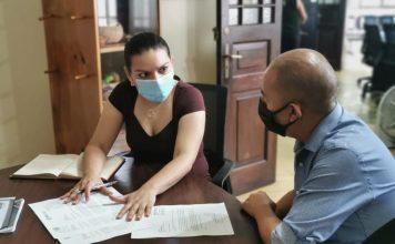 Gabriela Guzmán, subsecretaria, explica las recientes instrucciones sobre el programa al diputado Aldo Dávila, de Winaq.