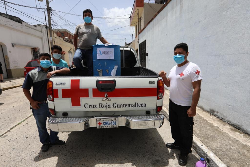 Miembros de la Crus Roja reciben el donativo de cloro.