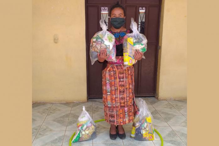 Una madre recibe alimentos no perecederos, el 21 de mayo pasado, distribuidos por SOSEP para niños beneficiarios del programa Hogares Comunitarios.