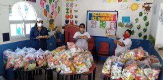 Personal del Programa Hogares Comunitarios en la entrega de alimentos a padres de los beneficiarios.