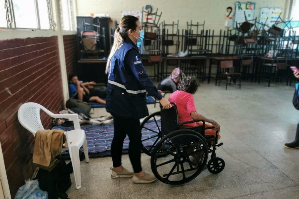 Una trabajadora de SOSEP ayuda en la movilización de una persona albergada.